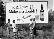 President Reagan Visits Ireland..Advertising Campaign.1984.04.06.1984.06.04.1984.4th June 1984..Availing of the opportunity of the President Reagan visit, the Whiskey manufacturers advertised their wares..Photo shows a large billboard encouraging RR (Ronald Reagan) to have a double. Passers by discuss the billboard.. Jameson's, Irish, Whiskey, jameson,
