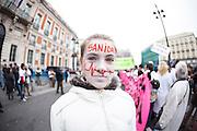 Belen Perez, a young woman with her face painted white with a diminishing ECG graph protesting against the spanish health privatization