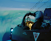 Flight Lieutenant Dave Slow of the elite 'Red Arrows', Britain's prestigious Royal Air Force aerobatic team, is seated in a BAE Systems Hawk jet aircraft simulator at the fast-jet flying training centre, RAF Valley, Anglesey, Wales. Like all fast-jet pilots, Flight Lieutenant Slow is required to complete this emergency drill every six months. The pilot is seated in his ejector seat as if in a real jet using back-projected computer graphics representing a generic landscape below. Each aviator proves they can cope with a series of failures that operators select: Engine, hydraulic failure or bird strike.  Apart from the aircraft fuselage, the high-tech facility loads malfunctions on a pilot that he could experience in reality. The version of Hawk that the Red Arrows fly is actually a primitive piece of equipment, without computers or fly-by-wire technology.