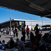 MORIA, GREECE - SEPTEMBER 10: Displaced asylum-seekers find new shelter at a Lidl parking lot as fires which started Tuesday night continue to rage into Thursday morning inside of Moria camp on September 10, 2020 in Moria. According to UNHCR, current numbers say the asylum-seekers displaced from the encampment are around 12,000. (Photo by Byron Smith/Getty Images)