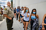 10 JULY 2020 - DES MOINES, IOWA: Black Lives Matter protesters walk past Polk County Sheriff's Department Captain VANHOOZER in front of the Polk County Criminal Court. He was telling them to leave the front of the courthouse. About 75 people, members and supporters of Black Lives Matter gathered at the Polk County Courthouse to protest law enforcement harassment of Black Lives Matter. They also showed support for several members of BLM who made their first appearance in court following their arrest at a BLM protest last week. BLM has become very active in Des Moines in the wake of the police killing of George Floyd in Minneapolis in May.      PHOTO BY JACK KURTZ