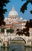 ITALY, ROME The Vatican State; St. Peter's Basilica with Michelangelo's dome rising above the Tiber  River and the Ponte San Angelo bridge
