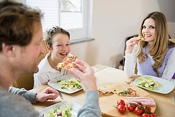 Family eating pizza and salad at home