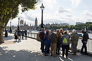 With the Houses of Parliament over the far side of the Thames river, a tour group pauses to hear about the capital from their leader on the Southbank, on 12th September 2017, in London, England.