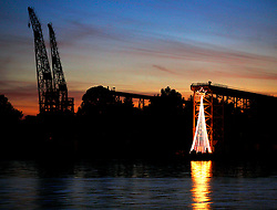Lights in the shape of a Christmas Tree glows in the shadow of the massive cranes along the Mare Island waterfront on Christmas Eve.  Photo ©2009 by Kim Kulish Photography