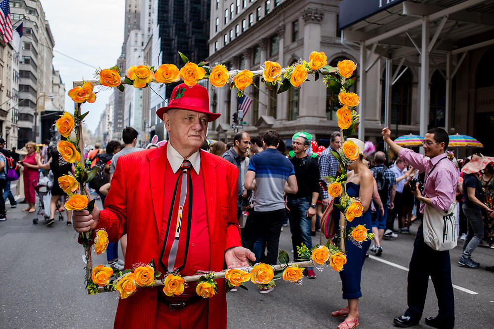 New York, NY - April 16, 2017. A man in red carries a large frame covered in orange flowers as if he were a painting  at New York's annual Easter Bonnet Parade and Festival on Fifth Avenue.