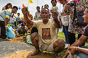 13 MAY 2013 - BANGKOK, THAILAND:  A man sells blessed rice seeds he collected at the Royal Ploughing Ceremony. After the ceremony, thousands of Thais, mostly family formers, rush onto the ploughed ground to gather up the blessed rice seeds sown by the Brahmin priests. The Royal Plowing Ceremony is held Thailand to mark the traditional beginning of the rice-growing season. The date is usually in May, but is determined by court astrologers and varies year to year. During the ceremony, two sacred oxen are hitched to a wooden plough and plough a small field on Sanam Luang (across from the Grand Palace), while rice seed is sown by court Brahmins. After the ploughing, the oxen are offered plates of food, including rice, corn, green beans, sesame, fresh-cut grass, water and rice whisky. Depending on what the oxen eat, court astrologers and Brahmins make a prediction on whether the coming growing season will be bountiful or not. The ceremony is rooted in Brahman belief, and is held to ensure a good harvest. A similar ceremony is held in Cambodia.   PHOTO BY JACK KURTZ