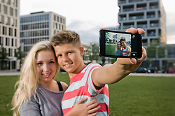 Portrait of teenage couple taking picture with smart phone, smiling