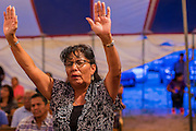 "12 JULY 2012 - FT DEFIANCE, AZ:   A woman prays at the 23rd annual Navajo Nation Camp Meeting in Ft. Defiance, north of Window Rock, AZ, on the Navajo reservation. Preachers from across the Navajo Nation, and the western US, come to Navajo Nation Camp Meeting to preach an evangelical form of Christianity. Evangelical Christians make up a growing part of the reservation - there are now more than a hundred camp meetings and tent revivals on the reservation every year. The camp meeting in Ft. Defiance draws nearly 200 people each night of its six day run. Many of the attendees convert to evangelical Christianity from traditional Navajo beliefs, Catholicism or Mormonism. ""Camp meetings"" are a form of Protestant Christian religious services originating in Britain and once common in rural parts of the United States. People would travel a great distance to a particular site to camp out, listen to itinerant preachers, and pray. This suited the rural life, before cars and highways were common, because rural areas often lacked traditional churches.  PHOTO BY JACK KURTZ"
