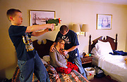 Corvin Prince shoots a toy gun while his mother Natasha Eggers is hugged by her husband Brandon Eggers in the hotel room in Spencer. The family has been living in the room for 8 days since a fire in the house in Coal City they moved into. (Photo by Jeremy Hogan)