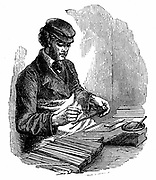 Setting lead (graphite) into grooved strip of cedar; a second strip of wood placed on top and glued, whole pencil placed in machine and rounded. BG Cohen, Great Prescott Street, London. Wood engraving 1872.