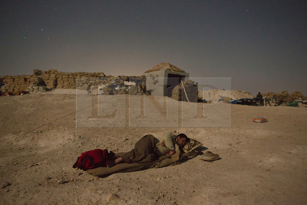 © Licensed to London News Pictures. 01/09/2015. Bashiqa, Iraq. A Kurdish peshmerga fighter takes advantage of a cool breeze by sleeping under the stars behind his unit's defensive position on Bashiqa Mountain, Iraq.<br /> <br /> Bashiqa Mountain, towering over the town of the same name, is now a heavily fortified front line. Kurdish peshmerga, having withdrawn to the mountain after the August 2014 ISIS offensive, now watch over Islamic State held territory from their sandbagged high-ground positions. Regular exchanges of fire take place between the Kurds and the Islamic militants with the occupied Iraqi city of Mosul forming the backdrop.<br /> <br /> The town of Bashiqa, a formerly mixed town that had a population of Yazidi, Kurd, Arab and Shabak, now lies empty apart from insurgents. Along with several other urban sprawls the town forms one of the gateways to Iraq's second largest city that will need to be dealt with should the Kurds be called to advance on Mosul. Photo credit: Matt Cetti-Roberts/LNP