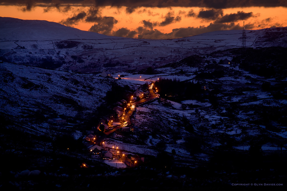 Street lights at Gallt y foel in the town of Deiniolen, glow in a wintry, snow covered landscape, with the lowest slopes of Yr Wyddfa (Snowdon) in the background in shadow against a warm orange sunset.