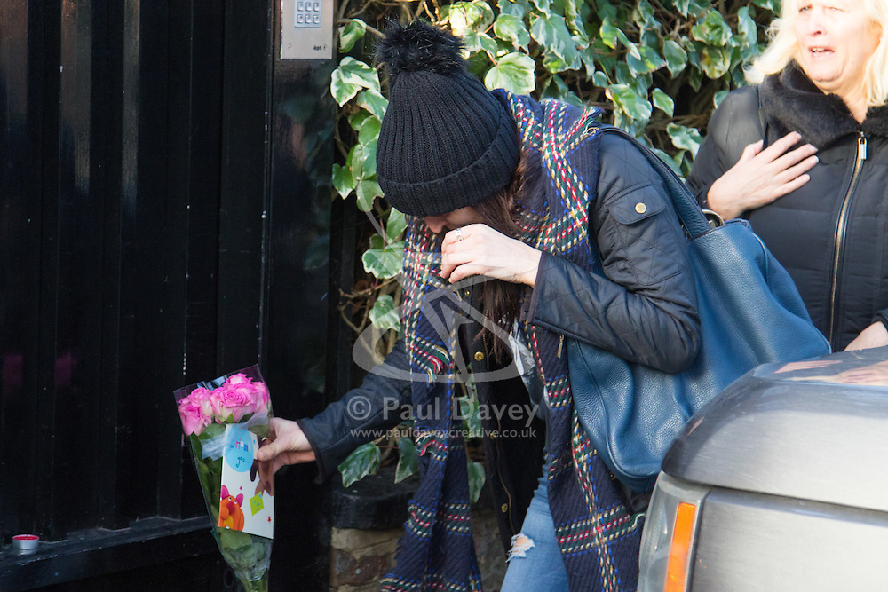 Highgate, London, December 26th 2016. Fans gather outside the London home of pop icon George Michael who died on Christmas day. PICTURED: A tearful woman lays flowers at Michael's gate.