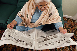 South Asian lady reading a newspaper,