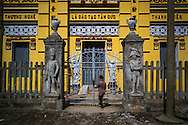 Yellow building facade near Phat Diem Cathedral with Napoleon-esque stone statues flanking the gated entrance, Ninh Binh Province, Vietnam, Southeast Asia