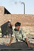 Young men are drying fresh painted leather under the Sun in front of the tannery where they work in Jajmau Industrial Area, Kanpur, Uttar Pradesh.