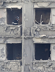 Fire service personnel inside Grenfell Tower in west London after a fire engulfed the 24-storey building yesterday morning.