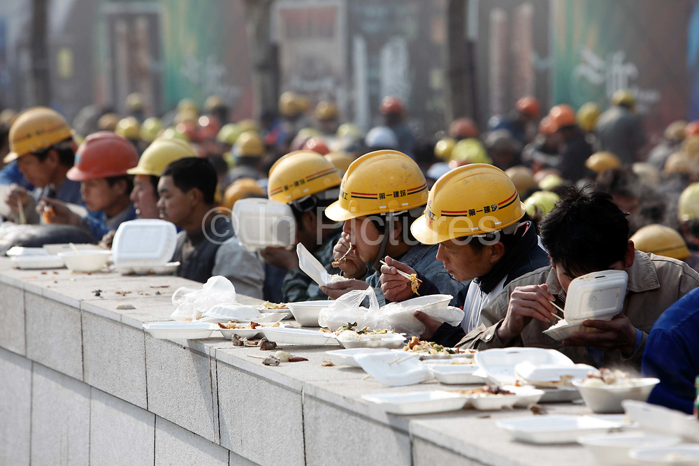Construction workers gather together on a makeshift eating area during lunch hour in Shanghai, China on 18 December, 2009.  While China owes much of its recent economic revival to the vast and cheap labor force made up by hundreds of millions of migrant workers, it is facing an uncertain future as the number of able bodied workers have passed their peak and wage continues to rise.
