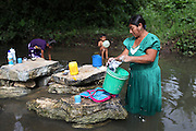 Cristina Peck, 47, Mopan Mayan cacao grower from San Jose, Toledo, does her family's laundry while her five-year old son Arden plays in the background and her nine-year old daughter Griselda helps out with the laundry. Cristina is married to Justino Peck who served as TCGA chairman from 1992 to 1997, once again from 2003 to 2010, and is currently the TCGA's liaison officer. Toledo Cacao Growers' Association (TCGA), San Jose, Toledo, Belize. January 25, 2013.