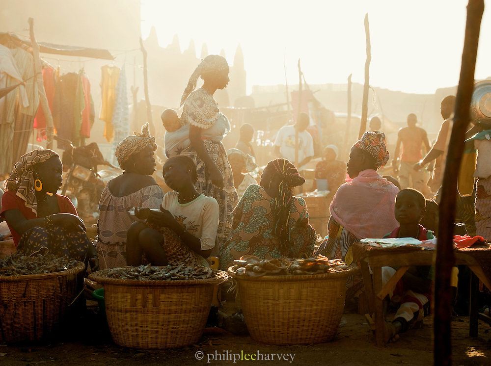 People buying and selling in the weekly market at dusk in Djenné, Mali