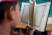A schoolboy recites Arabic verses from the Koran in a classroom at the Islamic Koom al-Bourit Institute for Boys in the village of Qum (Koom), on the West Bank of Luxor, Nile Valley, Egypt. Islam in Egypt is the dominant religion in a country with around 80 million Muslims, comprising 94.7% of the population, as of 2010. Almost the entirety of Egypt's Muslims are Sunnis, with a small minority of Shia and Ahmadi Muslims. The latter, however, are not recognised by Egypt.