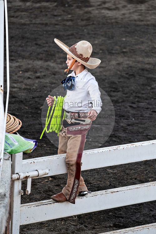 Eight-year-old Juan Franco, from the legendary Franco family of Charro champions, waits on a fence during a practice session in the Jalisco Highlands town of Capilla de Guadalupe, Mexico. The roping event is called Manganas a Pie or Roping on Foot and involves a charro on foot roping a wild mare by its front legs to cause it to fall and roll once. The wild mare is chased around the ring by three mounted charros.