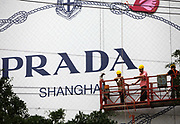 Workers ride on a lift in front of a large Prada billboard in Shanghai. China, on 06 July, 2010.  China is on track to become the largest luxury goods market, past the current leaders of United States and Japan, in the next five to ten years.