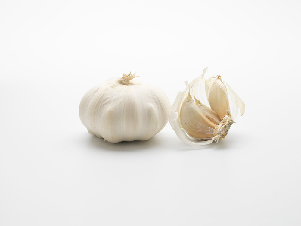 Whole garlic bulb and a split bulb on a white background
