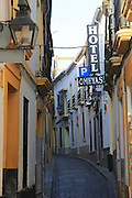 Hotel Omegas sign historic buildings in narrow street in old city centre of Cordoba, Spain