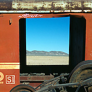 View of hills and wasteland through old train carriage window. Uyuni, Bolivia.