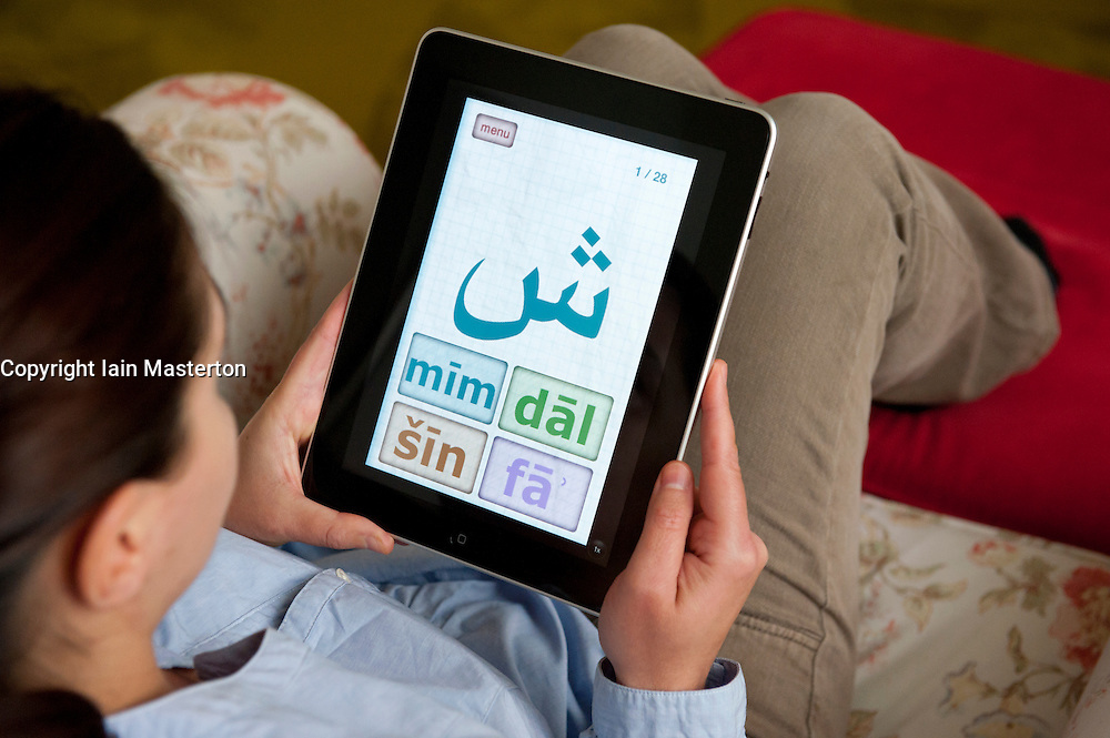 Female student learning Arabic language using education application on iPad tablet computer