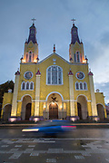 Low angle view of Church of San Francisco and car in blurred motion on Plaza de Armas Square, Castro, Chiloe Island, Chile