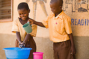 A boy and a girl in school uniforms wash their hands with soap.
