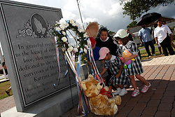29 August 2007. Lower 9th Ward, New Orleans, Louisiana. <br /> Second anniversary of Hurricane Katrina. Residents gather at the hurricane Katrina memorial in the Lower 9th Ward to remember those who perished when the industrial canal levee breached less than a mile from where they stand. Children laid teddy bears in memory of the children who perished. Many residents are struggling to return to the still derelict and decimated Lower 9th Ward.<br /> Photo credit; Charlie Varley/varleypix.com