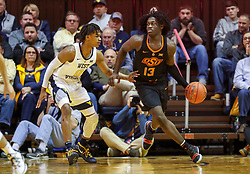 Jan 12, 2019; Morgantown, WV, USA; Oklahoma State Cowboys guard Isaac Likekele (13) dribbles while guarded by West Virginia Mountaineers guard Trey Doomes (0) during the second half at WVU Coliseum. Mandatory Credit: Ben Queen-USA TODAY Sports