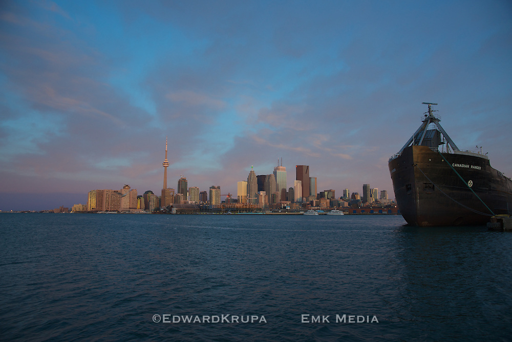 Toronto harbour and skyline in early sunny morning with the anchored cargo ship Canadian Ranger.