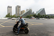 A motorcyclist rides a scooter through an intersection in the central business district of Chengdu, China, on Monday, Sept. 19, 2016. China faces unprecedented challenges as it restructures its economy away from old-line heavy manufacturing and toward consumption and services.