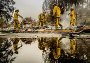 Cal Firefighters work on the remains of a home burned down during the Carr Fire on Harlan Dr. in Redding, Thursday, July 26, 2018.