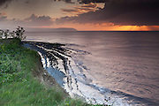 View of the setting sun as it shines through a heavy cloud with rays over the Bristol Channel, from the cliffs above Kilve Beach.