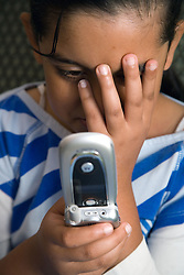 Child holding a mobile phone looking worried,