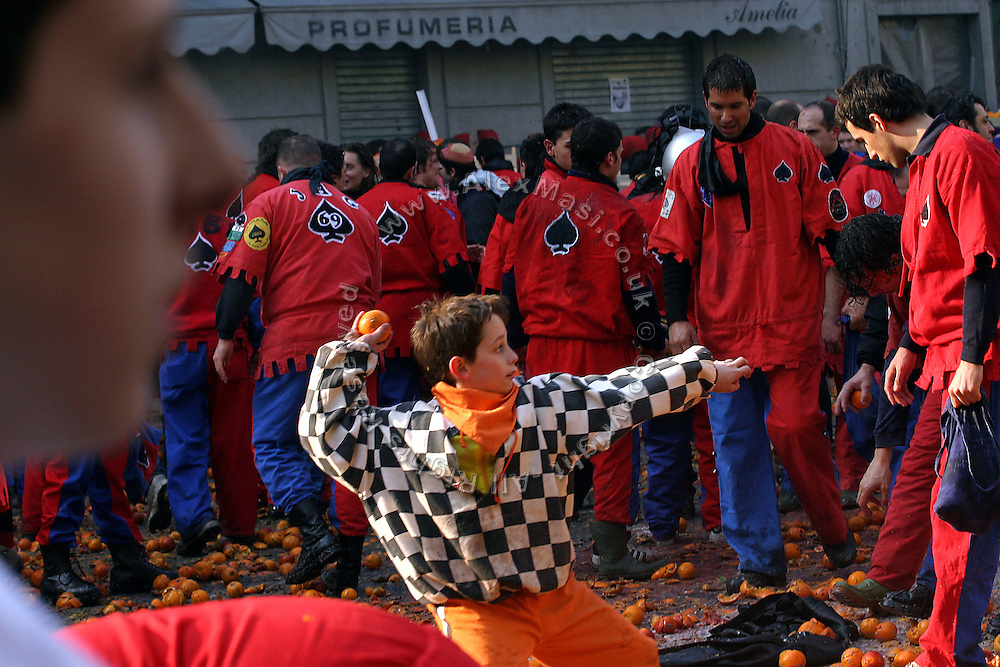 A young boy is throwing an orange towards a horse-van during The Battle of the Oranges in the City Square of Ivrea, pop. 30.000. During the days of the Carnival, the town becomes crammed with tourists coming to witness the event which finds its roots at the end of the XII Century, when the people led an insurrection against the local tyrant, Count Ranieri of Biandrate, who was exercising the 'jus primae noctis' rule (having the first night) on the local young brides. The battle to overthrow him is represented with a 3-day-fight between factions in which more then 400 tonnes of oranges are thrown. During the celebrations, food stalls, bands playing music, and parades are also present, giving it a typical Medieval atmosphere. ...