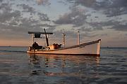 Crab fisherman on still waters at sunrise