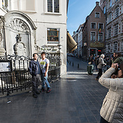 Tourists pose for photos on the street corner in front of the famous Mannekin Pis statue in central Brussels. The Mannekin Pis, a small bronze fountain sculpture of a naked little boy urinating into the fountain. Installed in about 1619 by Hiëronymus Duquesnoy the Elder, it is a cultural symbol of the city of Brussels and a famous tourism landmark.