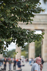 16 September 2021, Berlin, Germany: A man smokes at the historical site of Unter den Linden and Brandenburger Tor in Berlin.