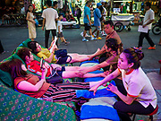 24 JULY 2018 - BANGKOK, THAILAND: Asian tourists get leg massages on Khao San Road in Bangkok. Khao San Road is Bangkok's original backpacker district and is still a popular hub for travelers, with an active night market and many street food stalls. The Bangkok municipal government plans to shut down the street market by early August because city officials say the venders, who set up on sidewalks and public streets, pose a threat to public safety and could impede emergency vehicles. It's the latest in a series of night markets and street markets the city has closed.  PHOTO BY JACK KURTZ
