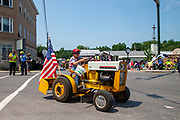 Lane Herring drives a vintage International Harvester Cub Cadet garden tractor in the Independence Day parade in Millville, Pennsylvania on July 5, 2021.