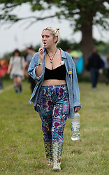 © Licensed to London News Pictures. 12/06/2015. Isle of Wight, UK.  A festival goer brushes her teeth at the Isle of Wight Festival 2015 on Friday Day 2.  Yesterday the weather was hot and Sunny.  Today rain is forecast.  This years festival include headline artists the Prodigy, Blur and Fleetwood Mac.  Photo credit : Richard Isaac/LNP