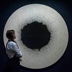 "© Licensed to London News Pictures. 19/06/2015. London, UK. A Sotheby's staff member looks at Latifa Echakhch's ""Tambour 39'""(est. £20k - £30k), at Sotheby's Impressionist, Modern & Contemporary Art preview, ahead of the sale on 24 June 2015. Leading the sale are Kazimir Malevich's, ""Suprematism, 18th Construction"" and Edouard Manet's ""Le Bar aux Folies-Bergère"".  Photo credit : Stephen Chung/LNP"