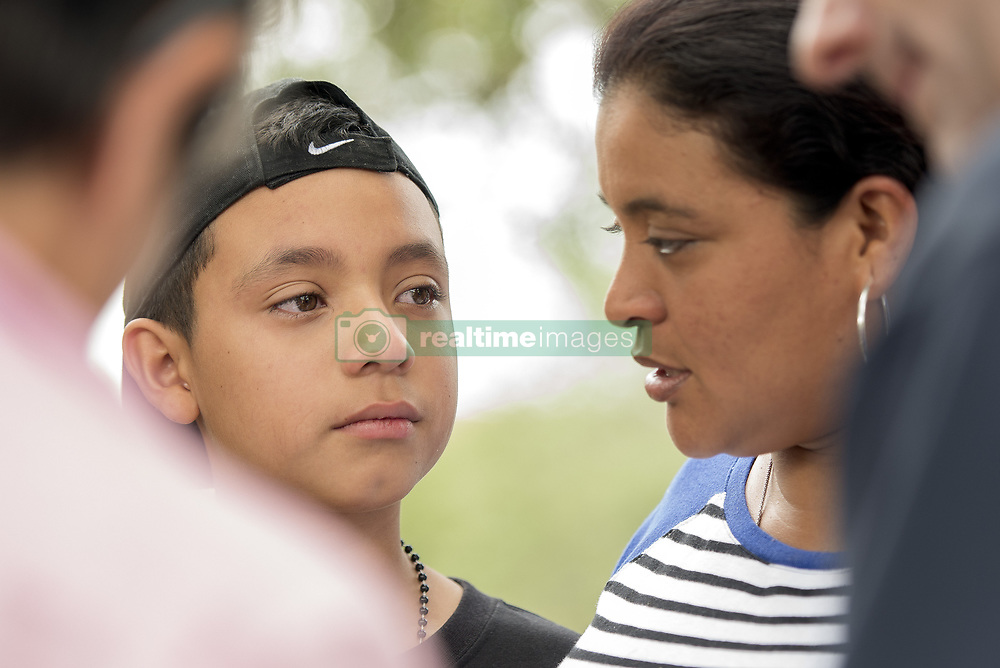 May 19, 2017 - Miramar, Florida, U.S - NICHOLAS MARTINEZ, 11, of Miami, sheds a tear after his mother, JENNY MARTINEZ, shares her story at a protest held outside the  U.S. Immigration and Customs Enforcement building in Miramar, Fla. in light of recent  'silent raids' where immigrents were arrested during scheduled check-ins. Jenny Martinez fled domestic abuse in Ecuador Three months ago and wears an immigration ankle bracelet monitor. (Credit Image: © Orit Ben-Ezzer via ZUMA Wire)
